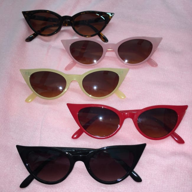 picture shows a selection of St Cyr cat eyes sunglasses laid out on pink cloth.
